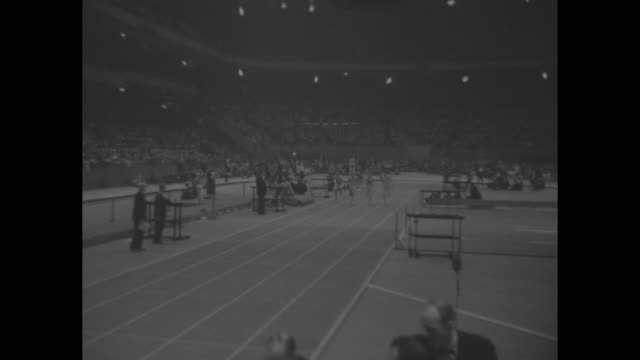four runners take off at sound of starter pistol, men race around indoor track at new york athletic club's track and field meet / vs jim fuchs shot... - shot put stock videos & royalty-free footage