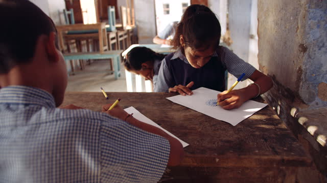 four school kids classmates in their art class as they draw and sketch different drawings on their piece of paper- christmas tree sant hat, face mask, diwali diya candle, etc - art class stock videos & royalty-free footage