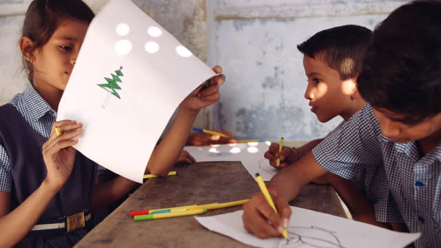 four school kids classmates in their art class as they draw and sketch different drawings on their piece of paper- christmas tree sant hat, face mask, diwali diya candle, etc - pencil icon stock videos & royalty-free footage