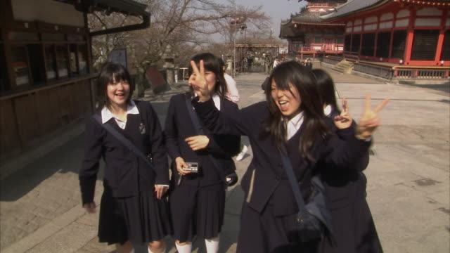 ms pan four schoolgirls laughing, kiyomizu-dera temple in background, kyoto, japan - japanese school uniform stock videos & royalty-free footage
