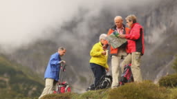 four senior hikers looking at map wide