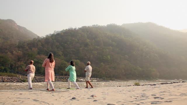 Four senior people doing yoga at riverbank, Ganges River, Rishikesh, Uttarakhand, India