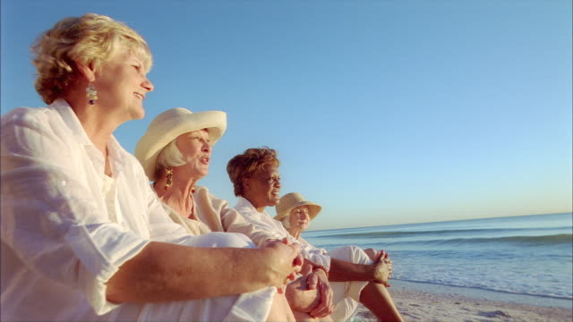 ms four senior women enjoying each others company while watching sunset beachside / cleatwater, florida, usa - female friendship stock videos & royalty-free footage