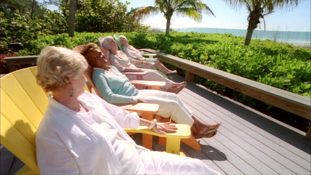 ms four senior women sitting on patio of beach side cottage enjoying beautiful day and each others company / cleatwater, florida, usa - retirement stock videos & royalty-free footage