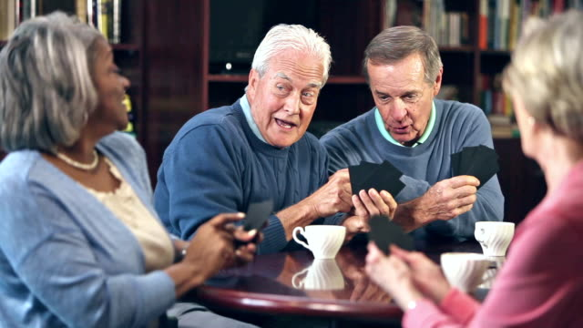 Four seniors drinking coffee, playing card game