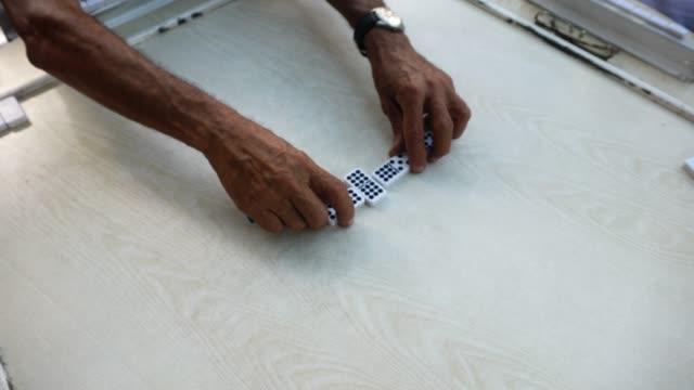 vídeos de stock, filmes e b-roll de quatro seniors maduro homem cubano jogando domino outdoor patio havana - organizações