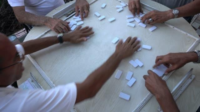 four seniors mature cuban man playing domino outdoor patio havana - cuban culture stock videos & royalty-free footage