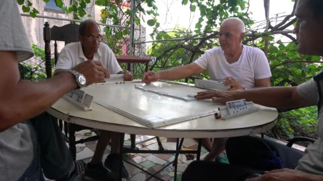 four seniors mature cuban man playing domino outdoor patio havana - dominoes stock videos & royalty-free footage