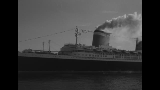 four shots from moving boat of ss united states entering harbor / shot from moving boat of escorting tugboats / shot from moving boat of passengers... - normandy stock videos & royalty-free footage