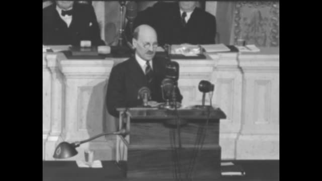 Four shots of British Attlee standing at podium on Speaker's Rostrum in House Chamber giving speech about his hopes for the future and things shared...
