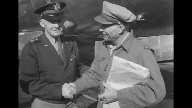 Four shots of General Henry Hap Arnold Chief of Army Air Forces shaking hands with Colonel Clarence Irvine next to B29 Superfortress airplane /...