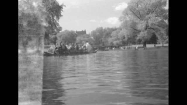four shots of group of small group of people floating in boat on pond / note: exact year not known - pond stock videos & royalty-free footage