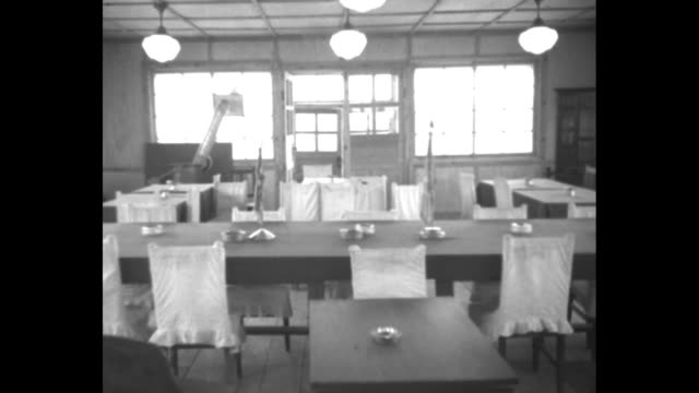 stockvideo's en b-roll-footage met four shots of inside empty negotiating shed / two shots of us mp inside empty shed holding up small flags on table / north korean communist liaison... - mp