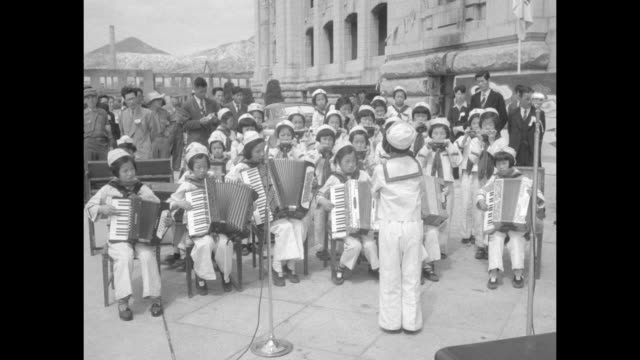 four shots of korean girl conducting band of korean teen and preteen girls all wear sailor suits / crowd of children listening / korean girl... - korea stock-videos und b-roll-filmmaterial