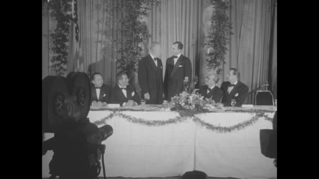 four shots of marshall on left standing with secretary of defense at banquet table talking and posing for photo opportunity other men sitting at... - segretario della difesa video stock e b–roll