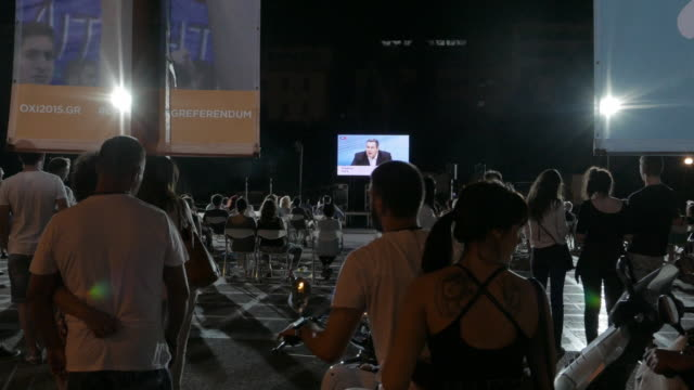 Four shots of people watching an open air TV broadcast announcing the referendum results over European bailout terms in Central Athens Night scenes...