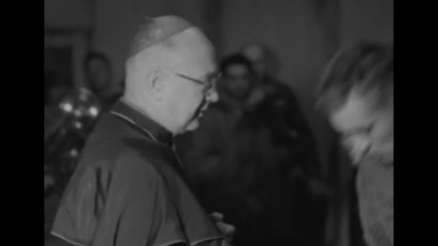 vidéos et rushes de four shots of soldiers walking up to cardinal francis spellman and taking his hand many kissing ring on his finger / group of soldiers holding hymn... - actualités cinématographiques