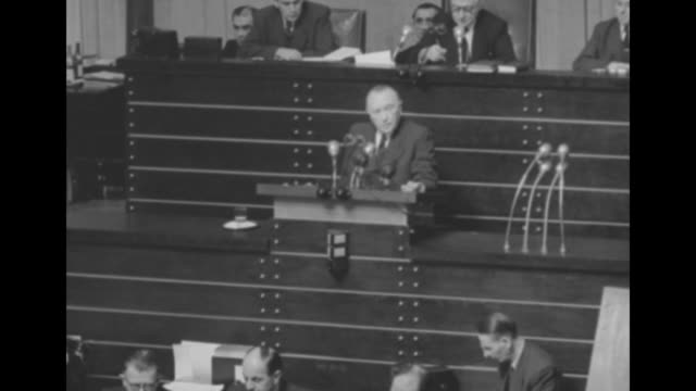 Four shots of West German Chancellor Konrad Adenauer standing at rostrum speaking about approving pacts with US and Western European countries /...