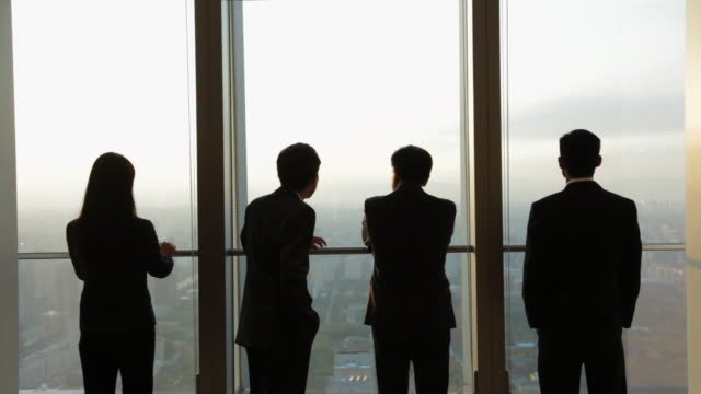 ms four silhouettes of business people looking at city view, standing by office window / beijing, china - asian colleague stock videos & royalty-free footage