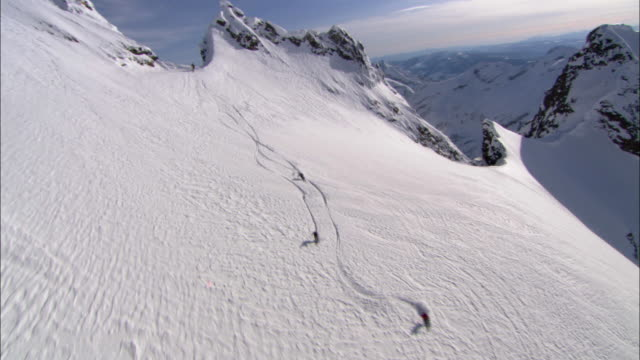 AERIAL, Four skiers gliding down mountainside, Cariboo and Monashee Mountains, British Columbia, Canada