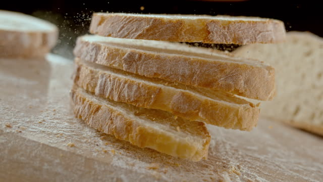 slo mo ld four slices of bread falling on the table - bread stock videos & royalty-free footage