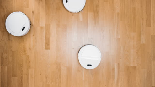 four small robot vacuum cleaners automatically cleaning the floor - vacuum cleaner stock videos & royalty-free footage