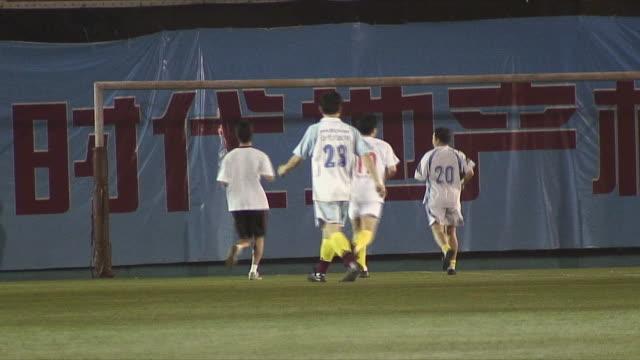 ws four soccer players warming up in field, guangzhou, china - ゴールポスト点の映像素材/bロール