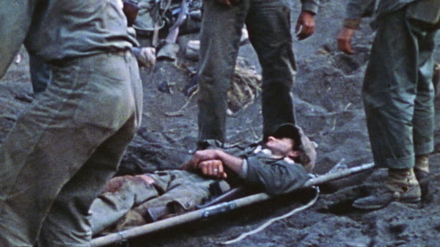 four soldiers carrying a comrade on a stretcher to get attention from medics at a campsite / iwo jima, japan - battaglia video stock e b–roll