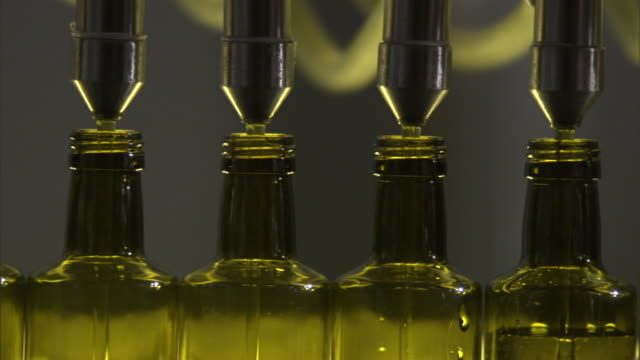 four spouts squirt olive oil into bottles in a factory assembly line. - olive oil stock videos & royalty-free footage