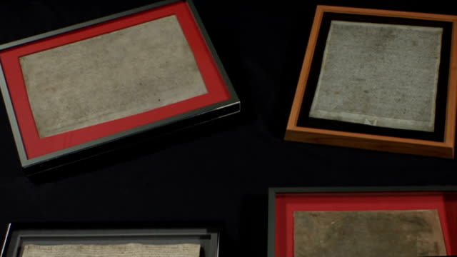 vídeos de stock e filmes b-roll de four surviving copies of the magna carta go on display at the british library; framed copies of the magna carta, two from the british library and one... - magna carta documento histórico