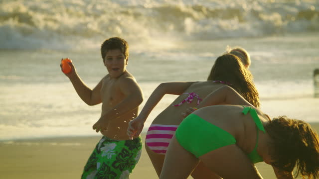 Four teen age children engaging in a water-balloon fight on the beach in slow-motion with the ocean surf behind them.