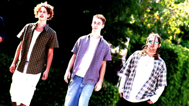 OVEREXPOSED CANTED MS PAN four teen boys walking outdoors with trees + bushes in background