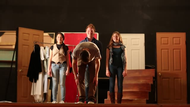 stockvideo's en b-roll-footage met four teenage actors bowing at the conclusion of a theater performance - toneel