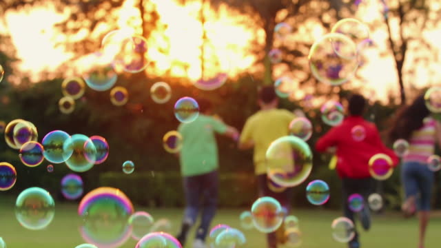 four teenage boys and girls enjoying bubble wand in the park, delhi, india - teenagers only bildbanksvideor och videomaterial från bakom kulisserna