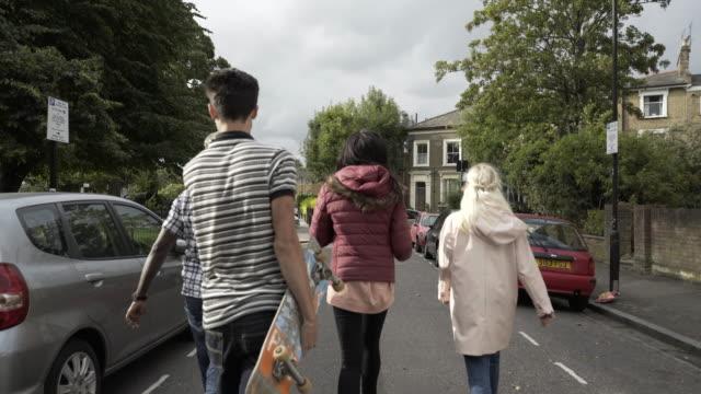 vídeos de stock, filmes e b-roll de four teens walking along a street. - ponto de vista de caminhada