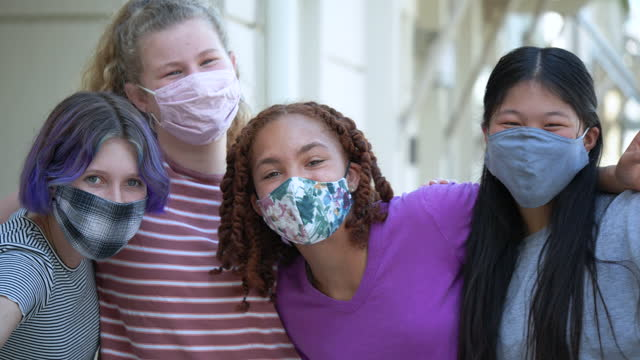 four tween girls  in face masks, smiling at camera - 12 13 years stock videos & royalty-free footage