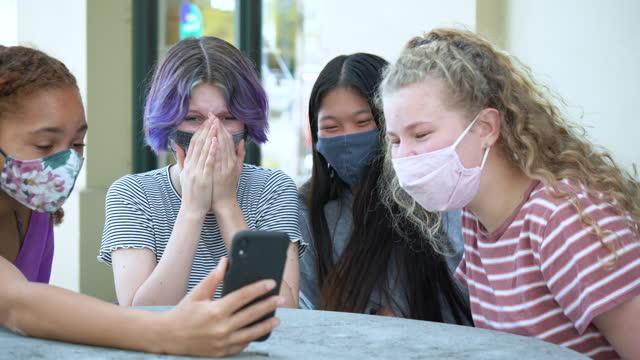 four tween girls laughing at smart phone, wearing masks - 12 13 years stock videos & royalty-free footage