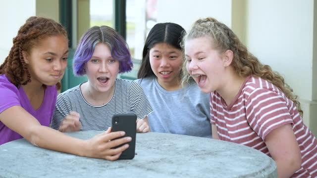 four tween girls looking at smart phone, laughing - 12 13 years stock videos & royalty-free footage