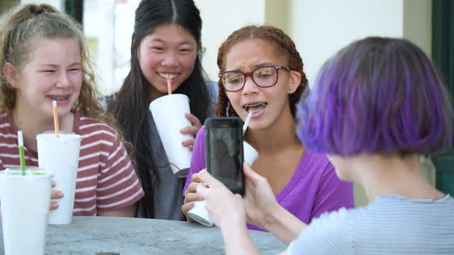 four tween girls on video call using smart phone - 12 13 years stock videos & royalty-free footage
