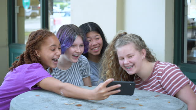four tween girls smiling at smart phone, on video call - 12 13 years stock videos & royalty-free footage