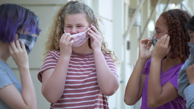 four tween girls standing outside putting on face masks - 12 13 years stock videos & royalty-free footage
