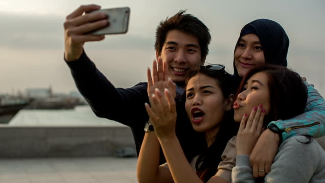 Four very young Korean tourists make selfie in front of the Museum of Islamic Art in Doha, Qatar