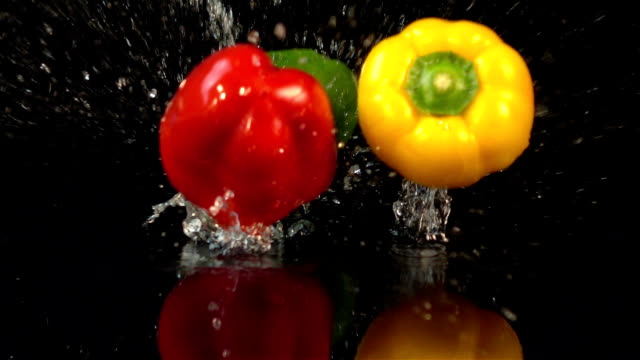 four videos of falling bell pepper in real slow motion - pepper vegetable stock videos and b-roll footage