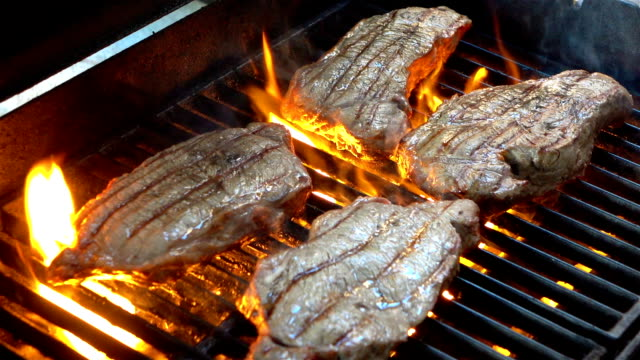 Four videos of grilling steaks on the fire-real slow motion
