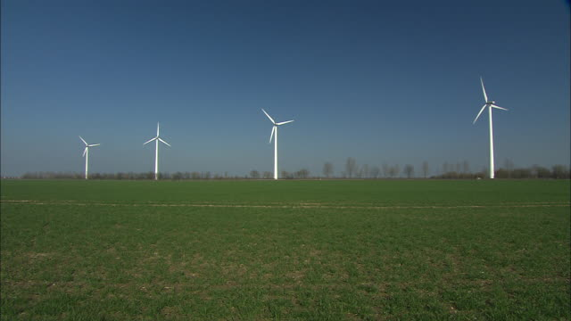 four wind turbines spin in a grassy field. - turbine stock videos & royalty-free footage