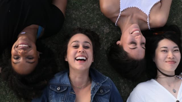four women friends laying down on the grass - quartet stock videos & royalty-free footage