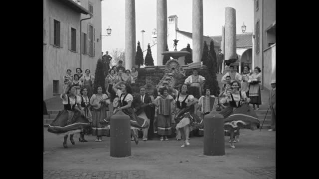 four women in costumes dancing in front of musicians in front of water pouring down an ornate fountain below a set of pillars / two women standing... - chicago world's fair stock videos and b-roll footage