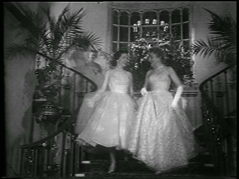 vidéos et rushes de b/w 1953 four women in formal dresses descending staircase indoors / newsreel - marches et escaliers