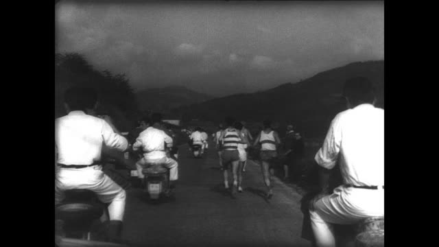 vídeos y material grabado en eventos de stock de four women in traditional dress carry banner reading 'i marathon internacional' / crowds line the small streets as marathon runners race by / men... - oficial deportivo