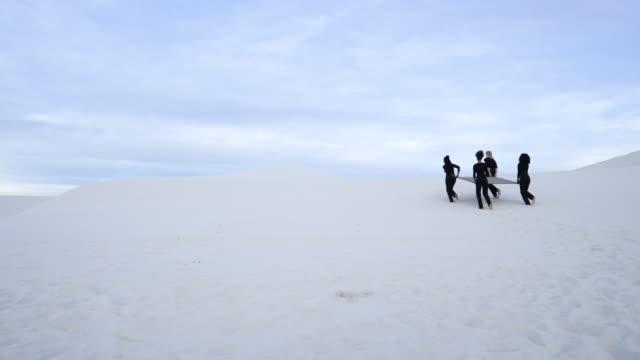 stockvideo's en b-roll-footage met four women lift grey square in desert, medium shot - initiatief